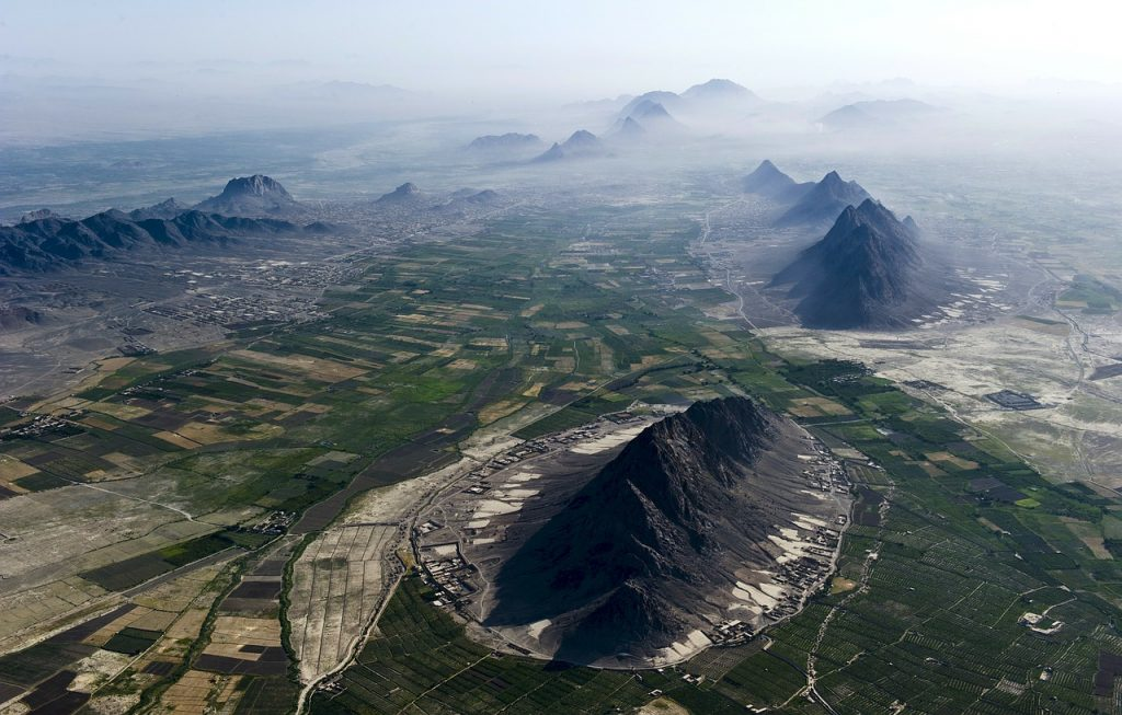 Aerial photo of farmed plains separated by dark mountains