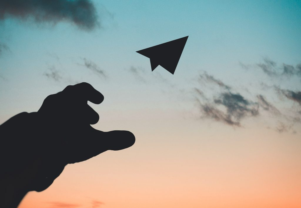A paper plane being thrown to the sky.