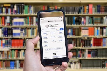 A mobile phone is held in one hand, with the Wikipedia home page shown on the screen. Library books can be seen in the background.