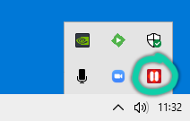 """Screenshot of Windows system tray, with a red and white """"pause"""" icon highlighted."""