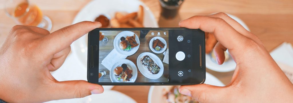Person holding a mobile phone and photographing their food (Credit: Eaters Collective)