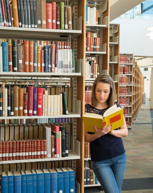 photo of woman reading book in McClay library