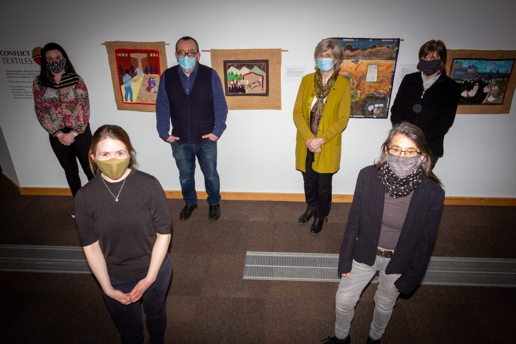 People facing camera with masks on with exhibition in the background.