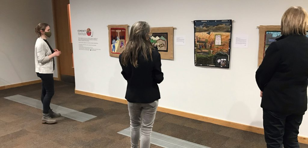 People viewing Conflict textiles exhibition at the McClay Library.